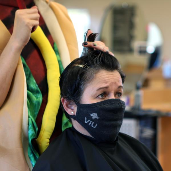 Dr. Deb Saucier, VIU President and Vice-Chancellor, receives a haircut at the VIU salon